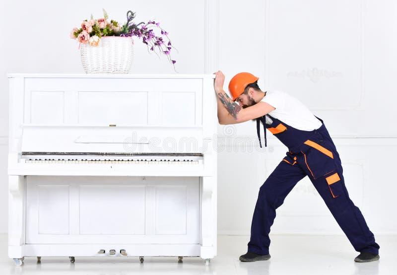 Mens met baardarbeider in helm en overallduwen, inspanningen om piano, witte achtergrond te bewegen Zware ladingenconcept royalty-vrije stock foto