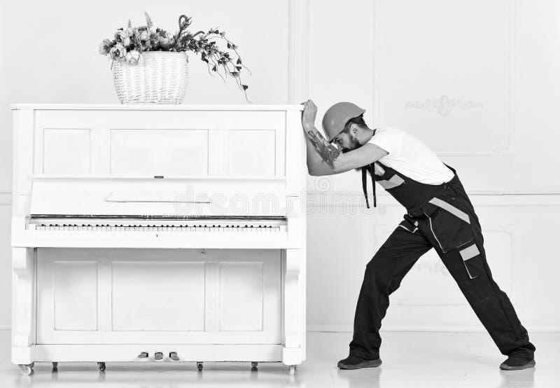 Mens met baardarbeider in helm en overallduwen, inspanningen om piano, witte achtergrond te bewegen Zware ladingenconcept stock foto's