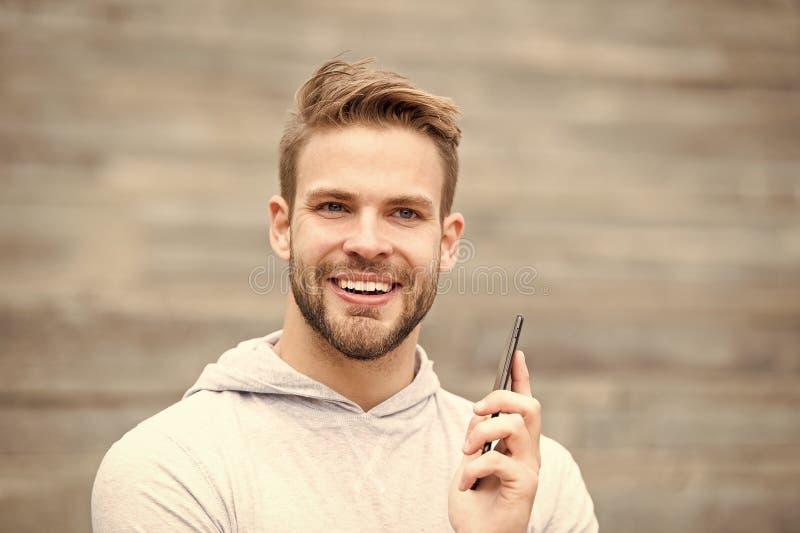 Mens met baardgangen met smartphone, stedelijke achtergrond met treden De mens met baard op het glimlachen gezicht spreekt op sma stock foto's
