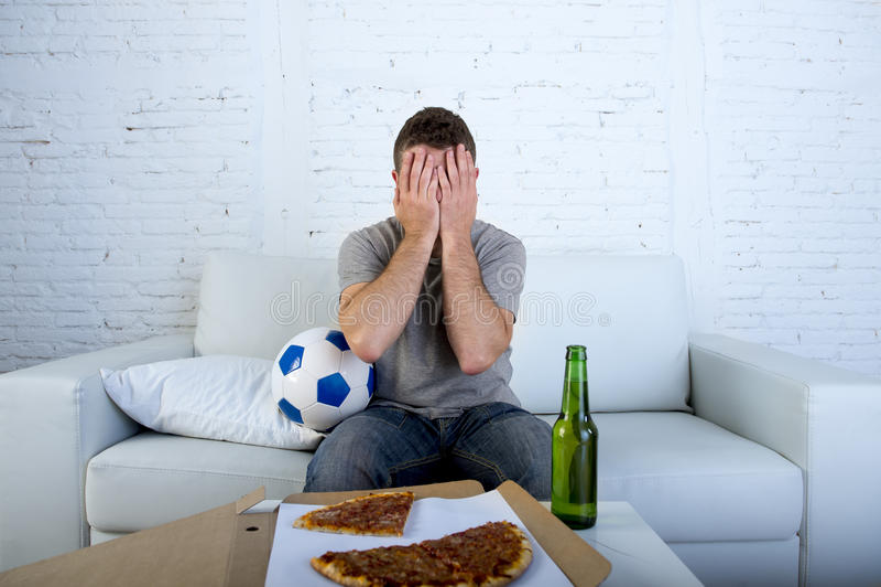 Mens met balpizza en bierfles het letten op voetbalspel op TV die die ogen behandelen droevig en voor mislukking of nederlaag wor royalty-vrije stock afbeeldingen