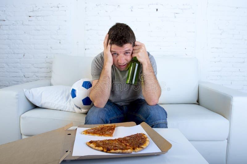 Mens met balpizza en bierfles het letten op voetbalspel op TV die die ogen behandelen droevig en voor mislukking of nederlaag wor royalty-vrije stock foto's