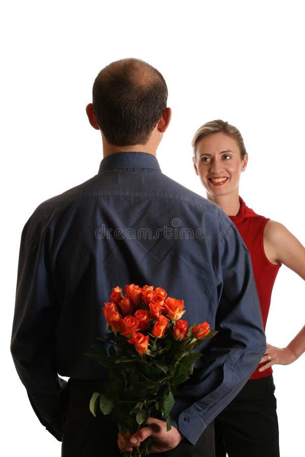 Mens met bloemen achter rug royalty-vrije stock afbeeldingen