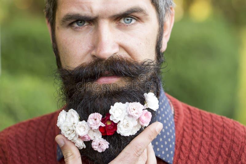 Mens met bloemen op baard stock foto's