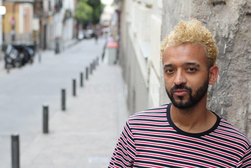 Mens met blond geverft afrohaar die in openlucht stellen stock fotografie