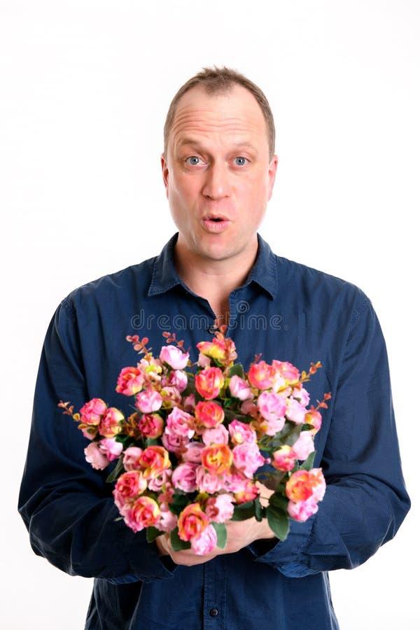 mens met bos van bloemen voor witte achtergrond stock fotografie