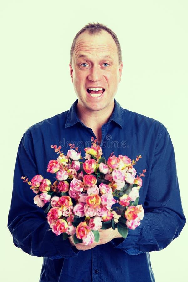 mens met bos van bloemen voor witte achtergrond stock afbeelding