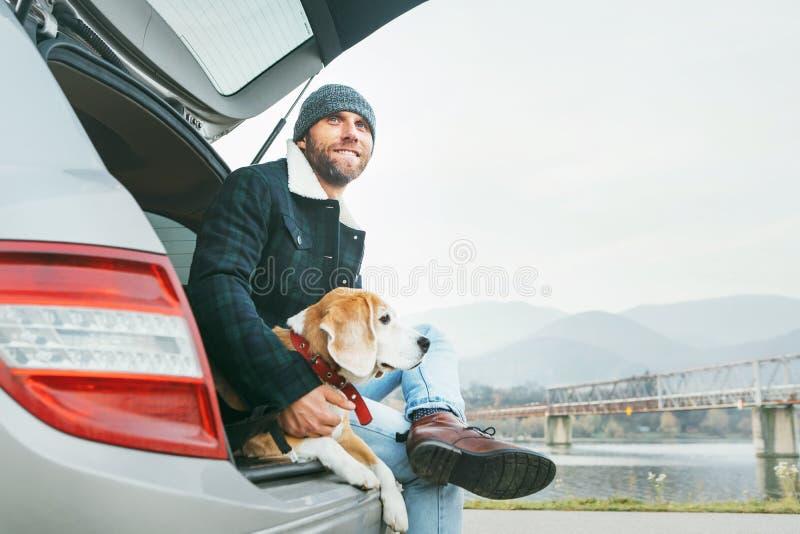 Mens met brakhond die samen in autoboomstam situeren Recent de herfstti stock afbeeldingen
