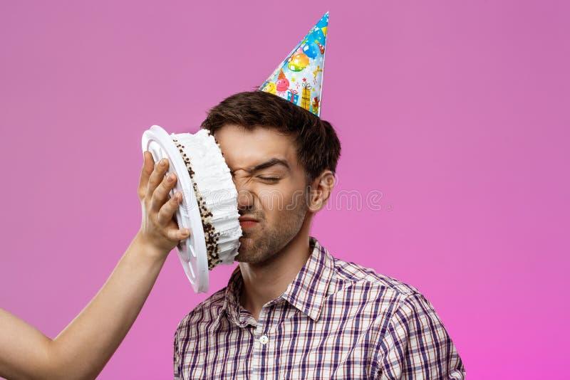 Mens met cake op gezicht over purpere achtergrond De partij van de verjaardag royalty-vrije stock afbeeldingen