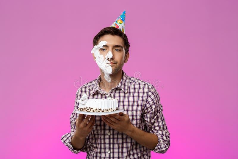 Mens met cake op gezicht over purpere achtergrond De partij van de verjaardag stock afbeeldingen