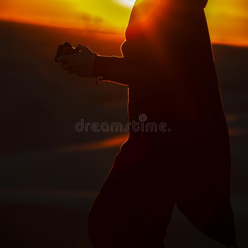 Mens met camera tegen zandduinen en zonsondergang stock afbeeldingen