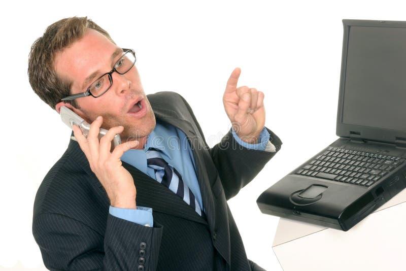 Mens met computerlaptop op zijn celtelefoon stock afbeeldingen