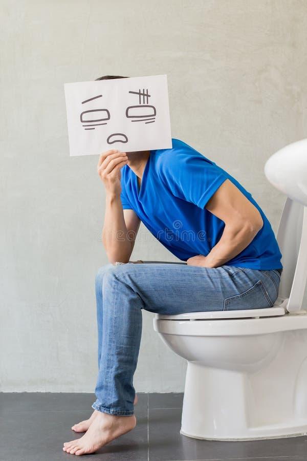 Mens met constipatie op toilet stock afbeeldingen