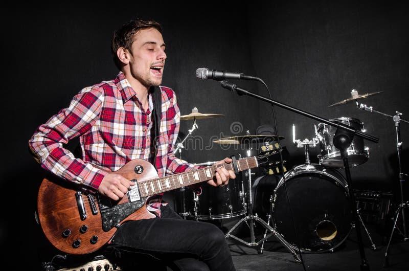Mens met de gitaar tijdens overleg stock foto