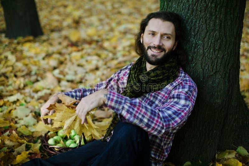 Mens met de herfstbladeren royalty-vrije stock afbeelding