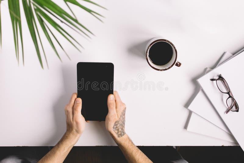 Mens met de tablet van de tatoegeringsholding op bureaulijst met, levering, bloem en kop van koffie Hoogste mening royalty-vrije stock afbeelding
