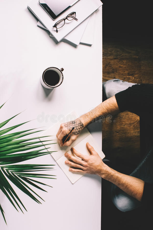 Mens met de tablet van de tatoegeringsholding op bureaulijst met, levering, bloem en kop van koffie Hoogste mening stock foto