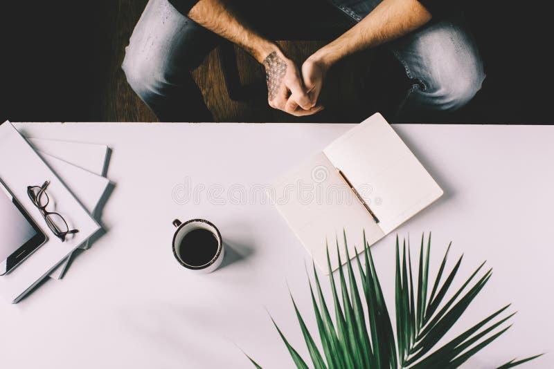 Mens met de tablet van de tatoegeringsholding op bureaulijst met, levering, bloem en kop van koffie Hoogste mening royalty-vrije stock afbeeldingen