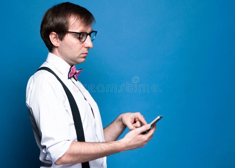 Mens met donker haar in roze overhemd met opgestroopte kokers, vlinderdas, zwarte bretel en glazen die smartphone gebruiken stock foto's