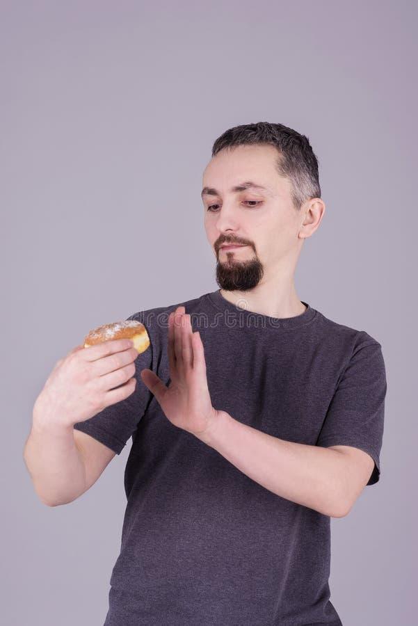 Mens met een baard die een broodje over grijze achtergrond eten stock afbeelding