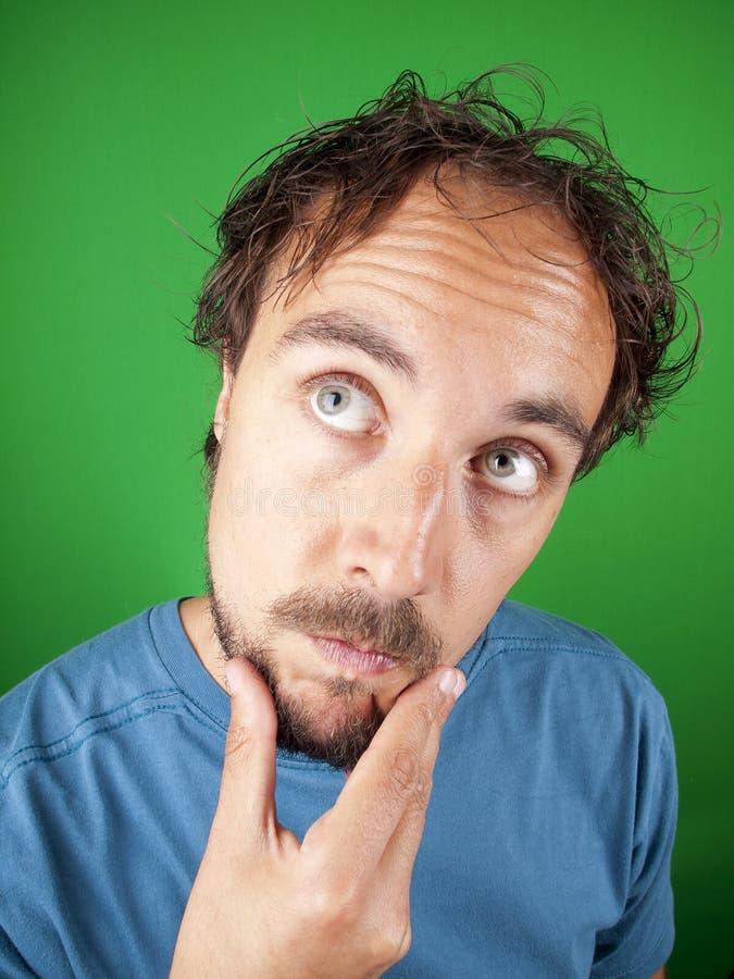 Mens met een baard die zijn kin strijken terwijl in diepe gedachten stock foto