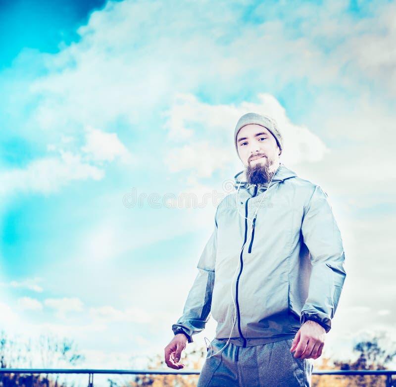 Mens met een baard en het dragen van een grijze bovenkledij, die zich tegen achtergrond van mooie blauwe sk bevinden stock afbeelding