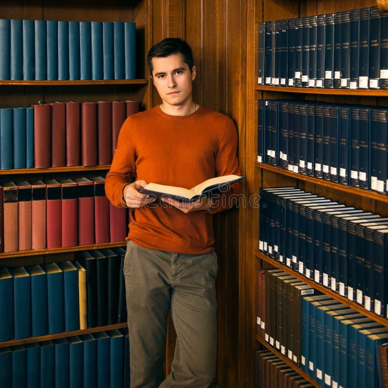 Mens met een boek die zich in de uitstekende bibliotheekplanken bevinden stock afbeeldingen