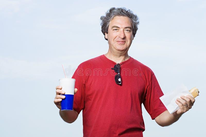 Mens met een drank en een hotdog royalty-vrije stock foto