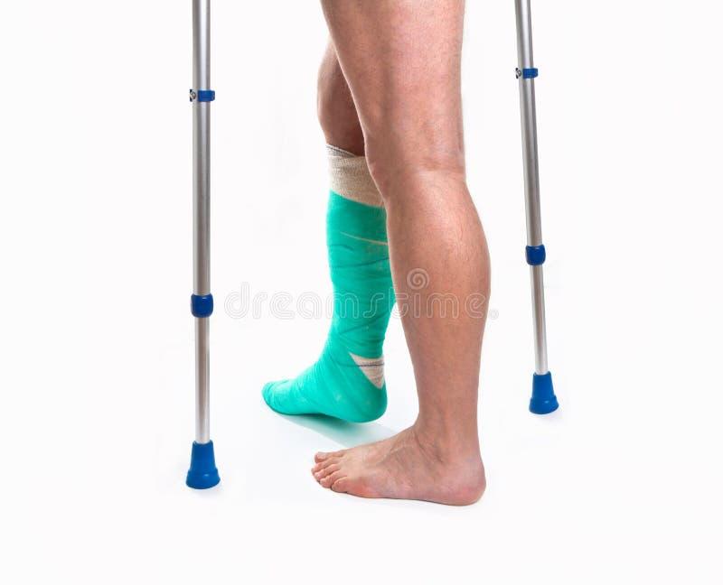 Mens met een gebroken been met Steunpilaren op een witte achtergrond stock afbeelding