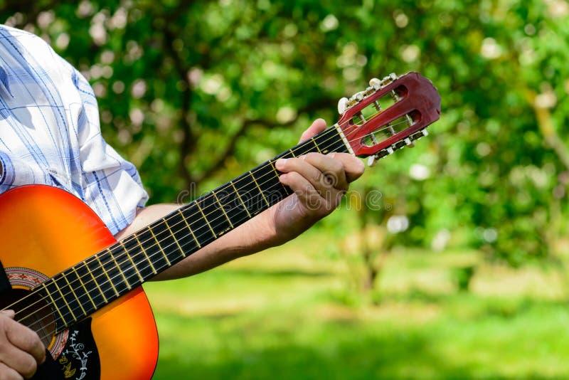 Mens met een gitaar in zijn handen stock foto