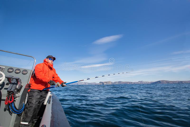 Mens met een hengel in zijn handen Rood jasje Sportenglazen royalty-vrije stock fotografie