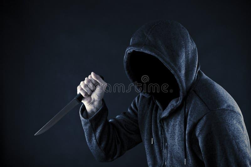 Mens met een kap met mes stock foto's
