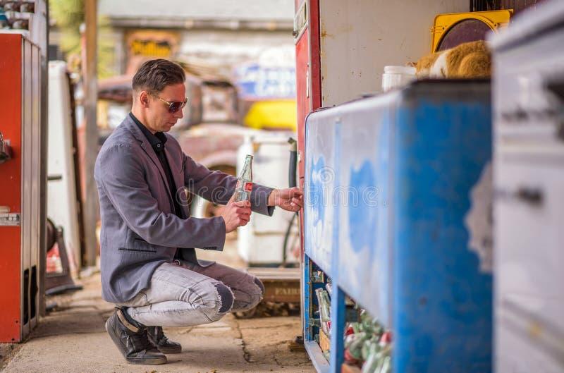 Mens met een lege Coca-colafles bij een uitstekende automaat royalty-vrije stock afbeeldingen
