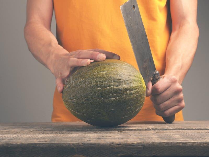Mens met een mes en een meloen royalty-vrije stock fotografie