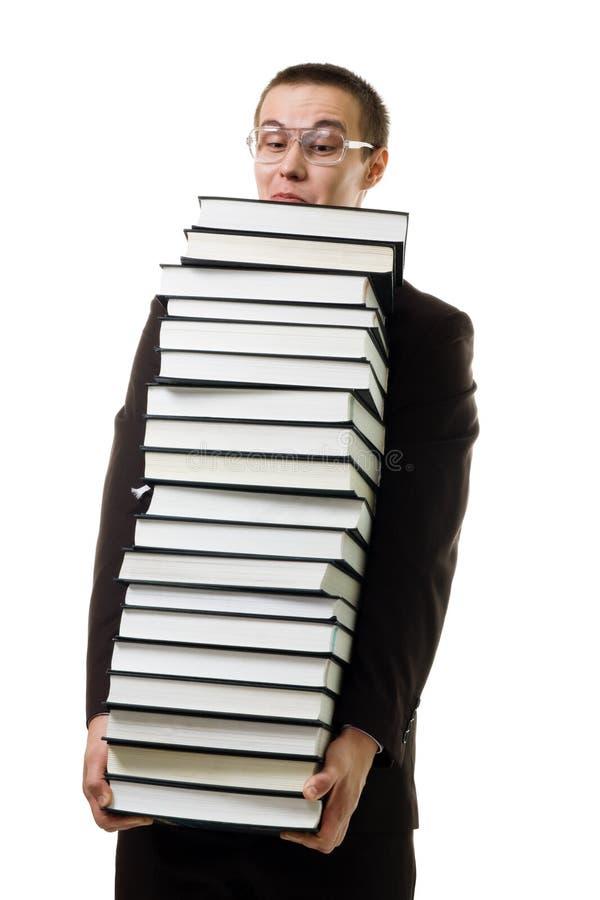 Mens met een reusachtige stapel van boeken stock afbeelding