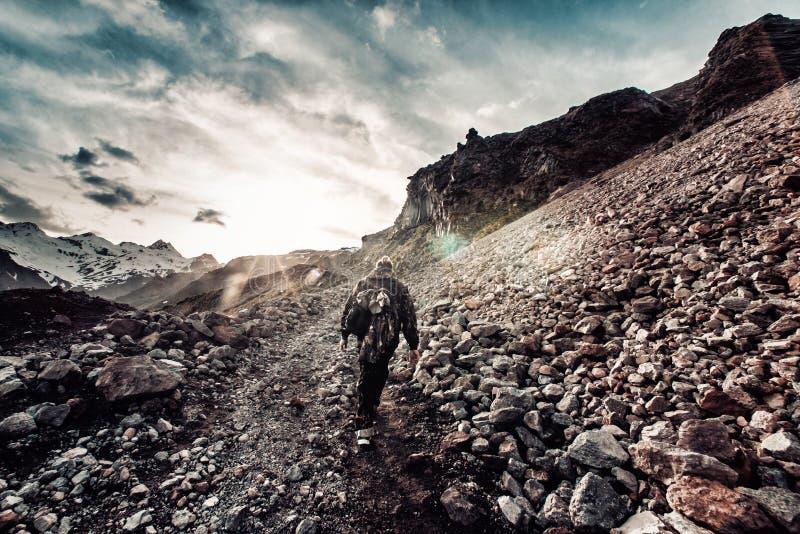 mens met een rugzak in camouflagestijgingen tot de bovenkant van de berg royalty-vrije stock foto