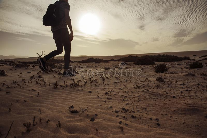 Mens met een rugzak die in de woestijn lopen stock foto's