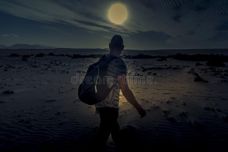 Mens met een rugzak die in de woestijn lopen stock afbeeldingen