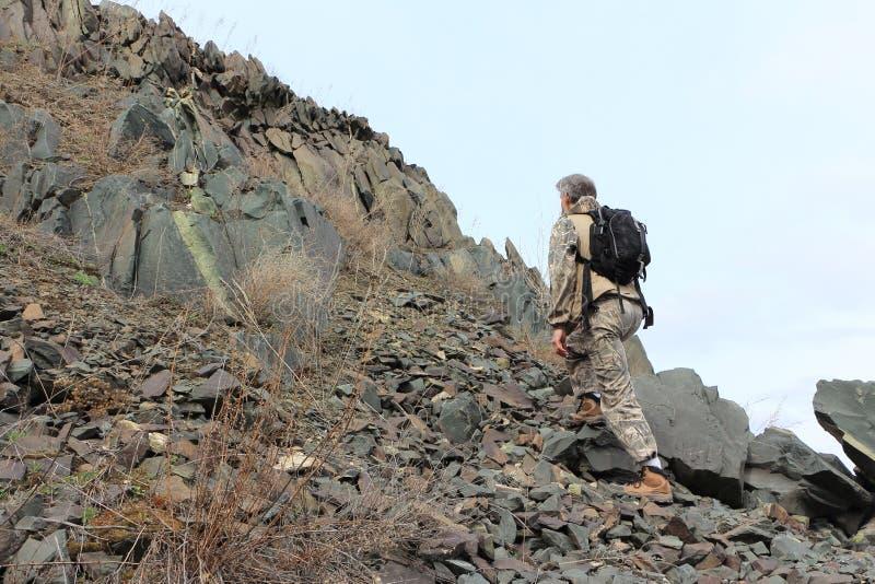 Mens met een rugzak die op stenen aan de berg beklimmen stock fotografie