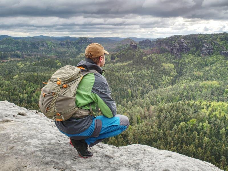 Mens met een rugzak en loopschoenentribunes bovenop een rots royalty-vrije stock foto's