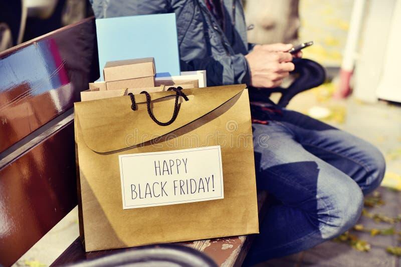 Mens met een smartphone en een zak met de tekst gelukkige zwarte vrijdag royalty-vrije stock fotografie