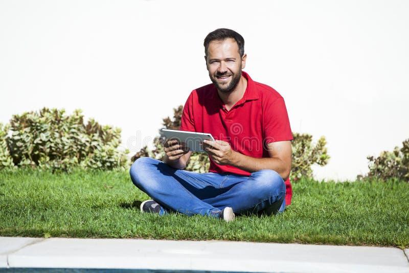Mens met een tablet, die op het gras zitten stock foto