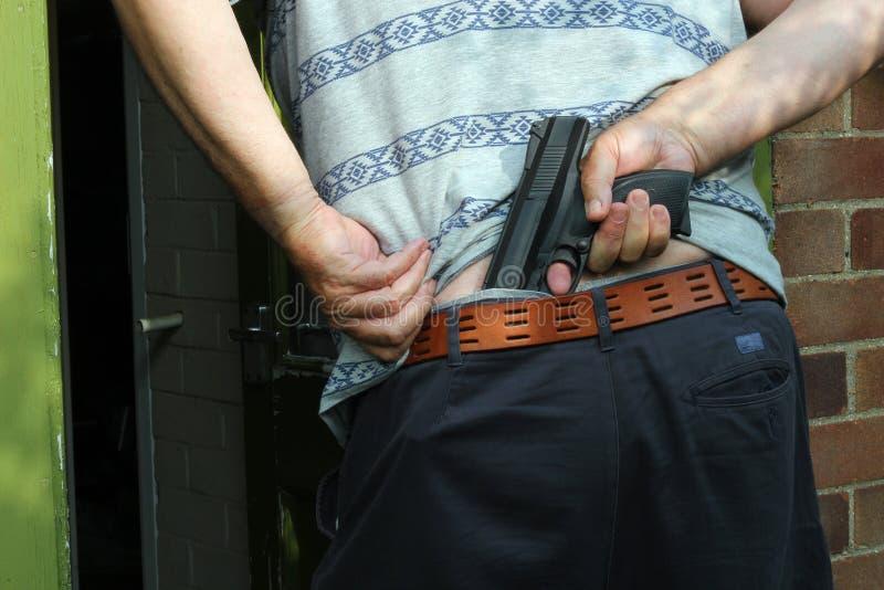 Mens met een verborgen wapen. stock fotografie