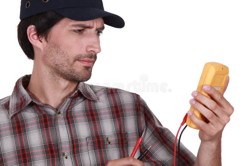 Mens met een voltmeter stock foto