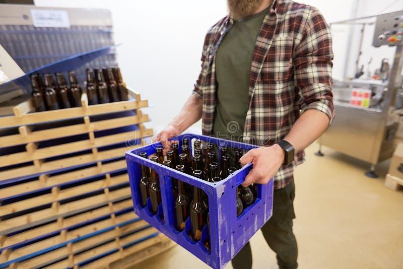 Mens met flessen in doos bij de brouwerij van het ambachtbier stock afbeelding