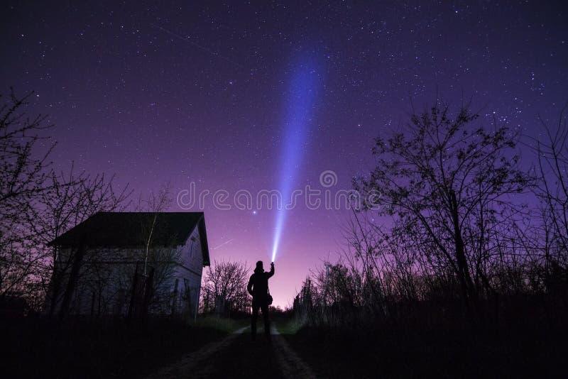 Mens met flitslicht dichtbij het huis en sterren op donkere hemel royalty-vrije stock afbeelding