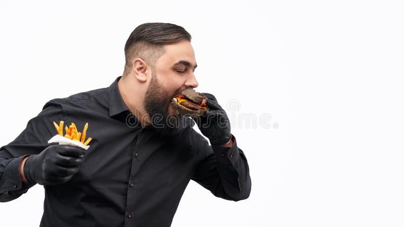 Mens met frieten die hamburger bijten royalty-vrije stock fotografie