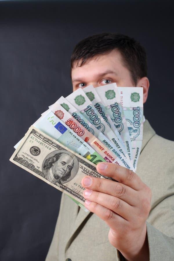 Mens met geld voor een zwarte achtergrond royalty-vrije stock afbeelding