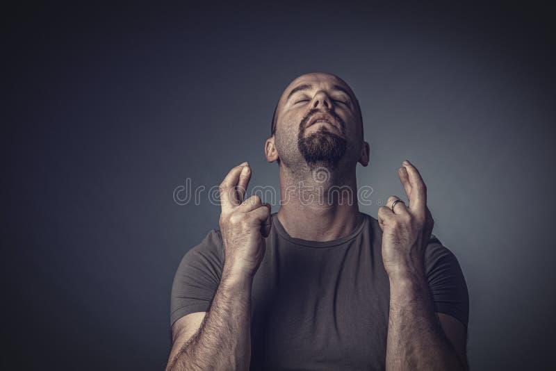 Mens met gesloten ogen en gekruiste vingers royalty-vrije stock foto's