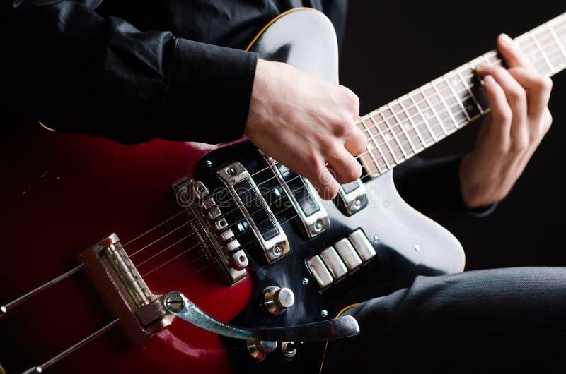 Mens met gitaar tijdens overleg stock fotografie