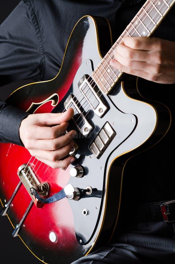 Mens met gitaar tijdens overleg stock afbeelding